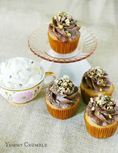 Cannoli Cupcakes filled with chocolate chip cannoli filling and topped with chocolate mascarpone frosting and pistachios