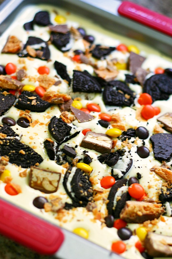 Halloween Candy Cheesecake Bars with Reese's Cups, Butterfinger Bars, Reese's Pieces, Oreos, Snickers, and Caramel - www.yummycrumble.com